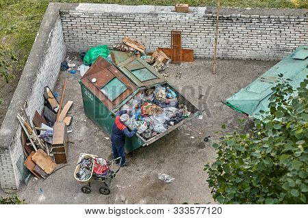 St. Petersburg, Russia - June 9, 2019: The Poor Are Looking For Recyclables In The Dumpster For Sale