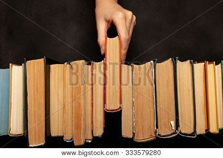 Hand Takes A Book. Vintage Paper Library Books For Reading, Education And Literature. Knowledge Is P