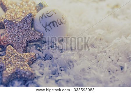 Chistmas Tree Ball With English Text - Merry Xmas- Lying Beside Glittery Stars As Greeting Card