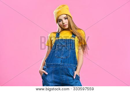 Portret A Pretty Girl In Denim Overalls And A Yellow Hat On A Pink Background. Fashionista Lady Stud