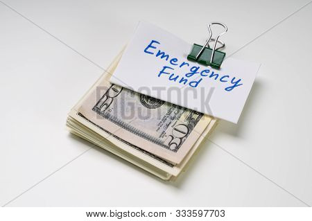 Emergency Fund Text On Card Over The Folded Bundle Of 50 Dollar Notes