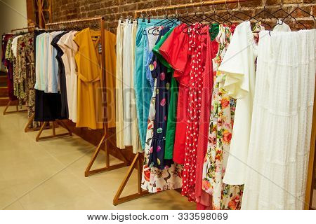 Colorful Collection Of Womens Clothes Hanging On A Rack.