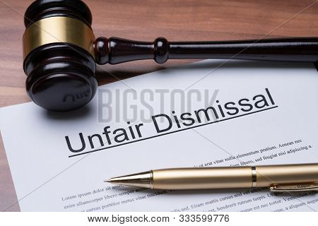 Documents Of Unfair Dismissal With Gavel And Pen On Wooden Desk In A Courtroom