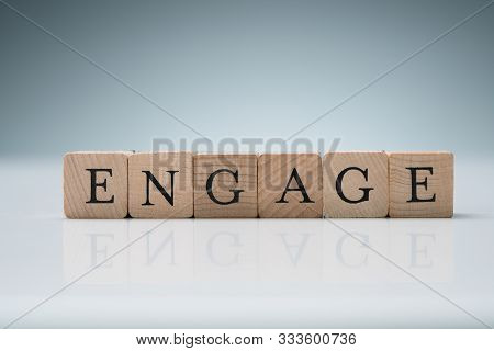 Close-up Of Wooden Blocks Arranged In A Row Showing Engage Text Over Reflective Desk