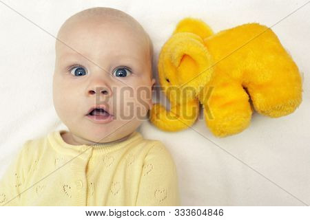 Сute Surprised Face Of Baby Infant With Yellow Elephant Toy In Bed, Listen, Have Conversation And Di