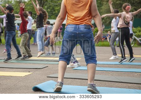 A Child On A Holiday Has Fun With Children. Children Perform An Exercise To Develop Muscle And Ligam