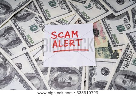 Background Of Dollar Bills With Scam Alert Text Written With Marker On Notepaper