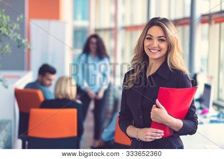 Business Woman With Folders Standing And Team Mates Working In Meeting Room At Office.