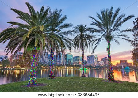 Orlando, Florida, USA downtown skyline at Eola Lake at dusk.