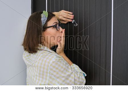Adult Woman Standing Near The Front Door And Looking Through The Peephole. Emotion Fear, Surprise, F
