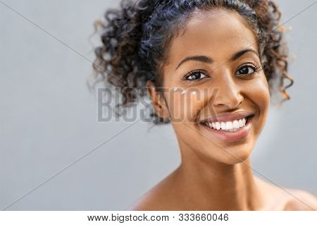 Young woman looking at camera with face moisturizer near eyes. Beautiful african girl applying face lotion on cheek. Beauty girl with perfect and healthy skin isolated on gray background.