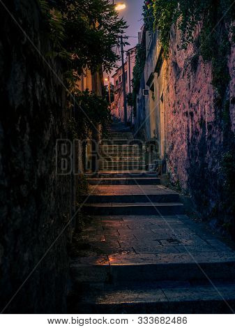 Stock Vertical Photo Of A Narrow Alley At Night In The City Of Dubrovnik, A Walled City