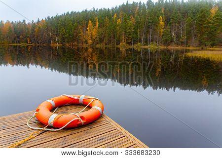 Orange Life Buoy Lying Near Finnish Lake With Mirror Image In Water