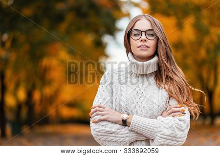 Pretty Cute Young Hipster Woman In A Trendy White Warm Knitted Sweater In Blue Jeans In Fashionable