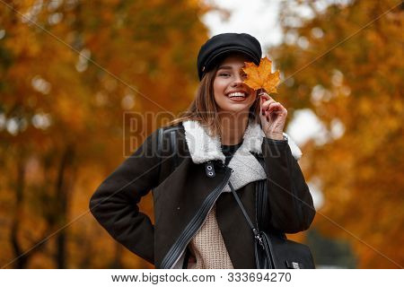 Funny Happy Young Woman In Stylish Outerwear In A Vintage Black Hat Posing In A Park. Cheerful Girl