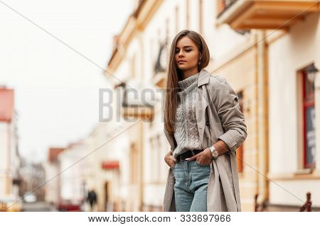Stylish Urban Young Woman In A Fashionable Knitted Sweater In A Elegance Trench Coat In A Blue Jeans