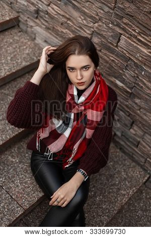 Attractive Pretty Young Woman In A Vintage Knitted Burgundy Sweater In Fashionable Black Leather Pan
