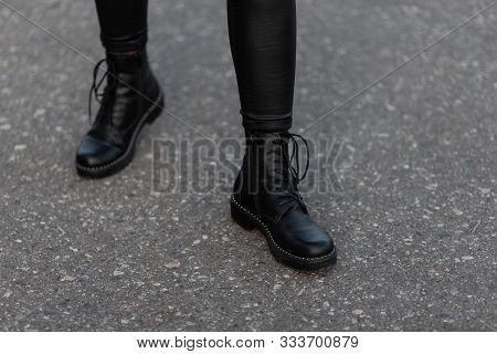 Modern Young Woman In Black Stylish Leggings In Fashionable Leather Boots Stands On The Road In The