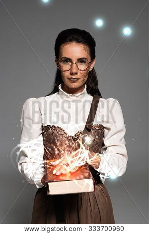 Pensive Steampunk Woman In Glasses Holding Book With Glowing Illustration Isolated On Grey