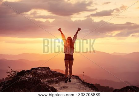 Happy Slim Girl Is Standing At Sunset Mountains With Raised Arms And Enjoying The View