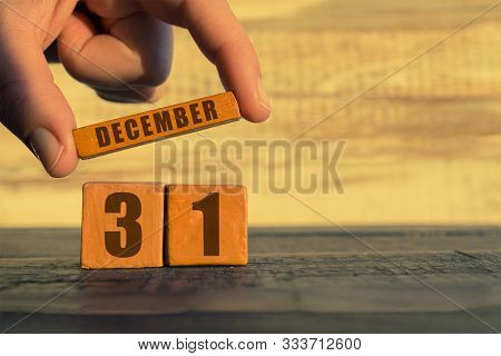 December 31st. Day 31of Month, Calendar On A Wooden Cube. A Womans Hand Puts The Name Of The Month O