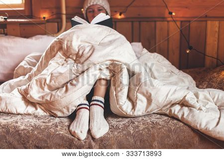 Young girl relaxing and reading book under warm duvet on cozy bed in log cabin in winter
