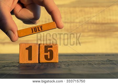 July 15th. Day 15 Of Month, Calendar On A Wooden Cube. A Womans Hand Puts The Name Of The Month On T