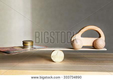 Car Cost, Conceptual Photo On A Gray Background A Model Of A Wooden Car On The Same Scale As Money,