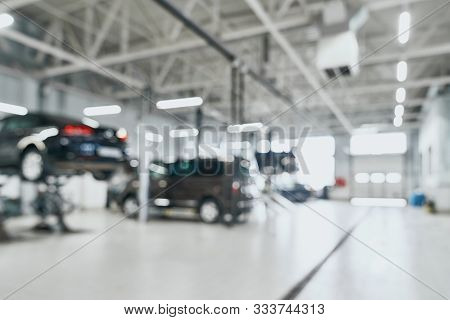 Repair Service Station With Lifted Modern Cars Being Under Maintenance And Technicians On Blurred Ba