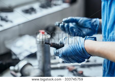 Auto Mechanics Hands In Protective Gloves Keeping Spark Plugs From Car Engine And Searching For Suit