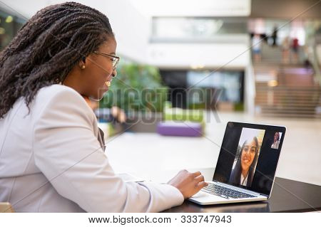 Happy Female Office Friends Talking Through Video Call. Business Women Using Digital Devices For Vid
