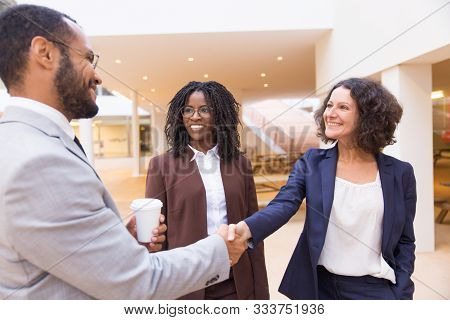 Happy Positive Business Partners Shaking Hands. Business Man And Women Standing In Office Hallway, S