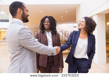Happy Business Partners Greeting Each Other. Business Man And Women Standing In Office Hallway, Shak