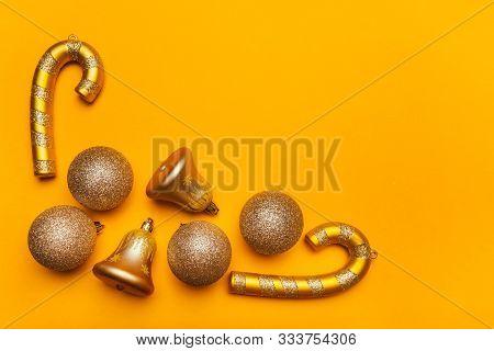 Golden Christmas Decorations: Balls, Bells, Lollipops On A Yellow Background. Festive Mood, Luxury P