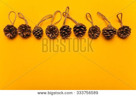 Christmas Decorative Cones On A Yellow Background. Festive Mood, Luxury Party, Winter Holidays, Craf
