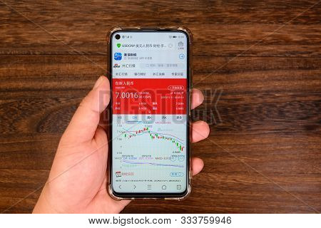 Zhongshan,china-november 11, 2019:chinese Man Checking The Usd To Rmb Rate On Mobile.