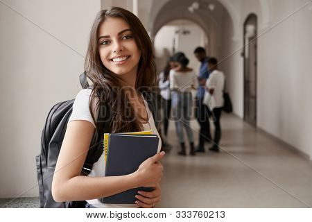 Side View Of Pretty Brunette Female Student Posing, Standing With Notes And Backpack On Corridor Of