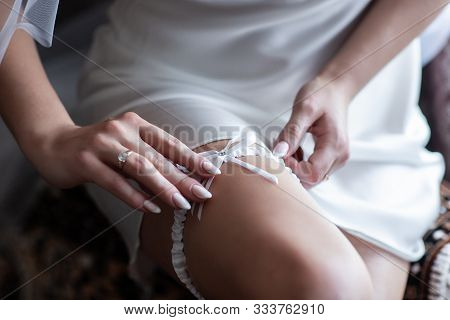 Bride Dresses Garter On The Leg. Bride Putting A Wedding Garter On Her Leg. Picture Of Beautiful Fem