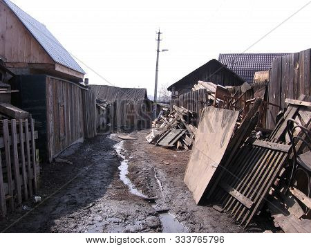 An Old Wooden Dirty House In A Siberian Untidy Village With Garbage And Scattered Things In An Unkem