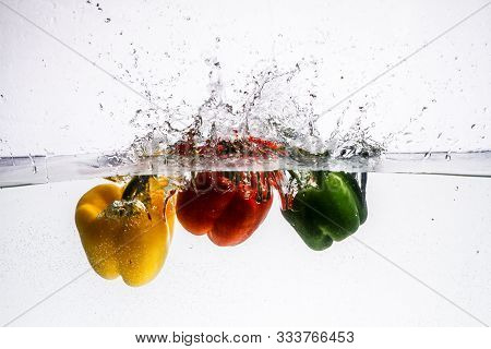 Three Peppers Falling In Water. Splash Of Water And Fruit Floating In It.