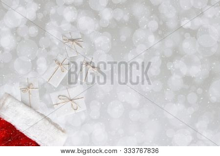 High angle photo of five Christmas presents wrapped in white paper and tied with white string and a stocking with a bokeh background a nd smnow effect.