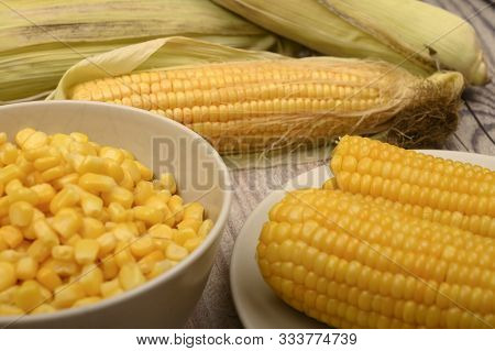 Two Boiled Ears Of Corn, Corn Kernels And Untreated Ears Of Corn On A Wooden Table. Fitness Diet. He