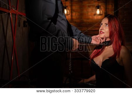 Leather Belt On The Neck Of Bdsm. Luxurious Chest In Black Underwear. A Woman Kneels In Front Of Her