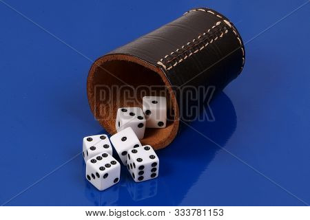 White Dice Falling From A Recumbent Leather Dice Cup On A Blue Background