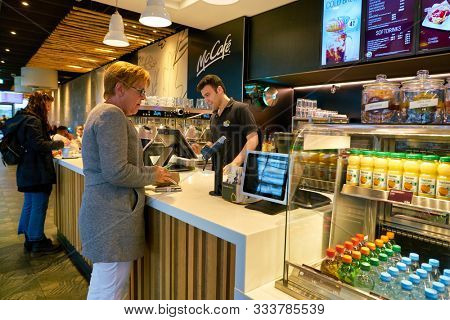 BERLIN, GERMANY - CIRCA SEPTEMBER, 2019: woman ordering a coffee at the counter in McCafe in Berlin.