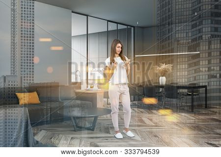 Woman With Coffee Standing In Stylish Living Room With Gray Walls, Comfortable Sofa With Coffee Tabl