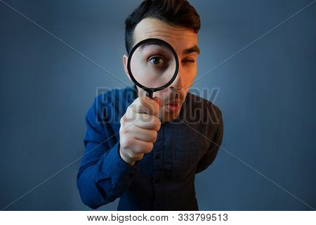 Curious Young Man With Magnifying Glass Isolated On Grey Background. Surprised Young Man Student Hol