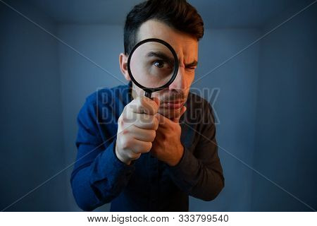 Surprised Young Man Student Holding Magnifying Glass Looking To Camera With A Pensive Emotion Isolat