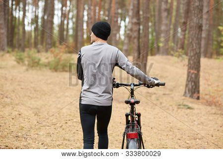 Back View Of Professional Cyclist Choosing Path In Forest, Looking Aside, Holding Sport Bicycle, Uni