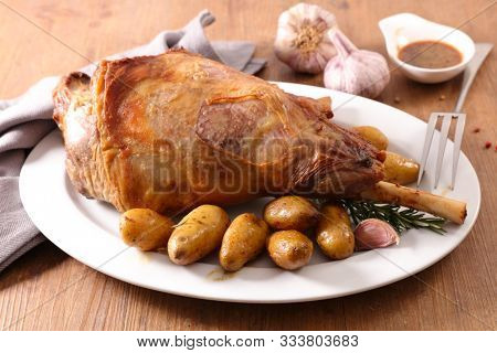 roasted lamb leg with potato and sauce on wood background